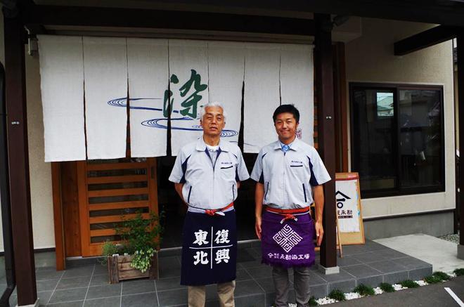 復興チャリティー前掛けを着ける永野仁社長(左)と、仁輝専務=仙台市若林区南染師町の永勘染工場
